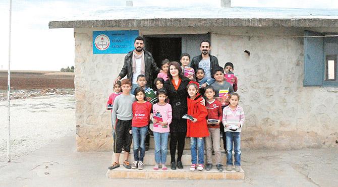 Rengin öğretmen ve arkadaşları mutluluk kolisi dağıttıkları öğrencilerle hatıra fotoğrafı çektirdi.