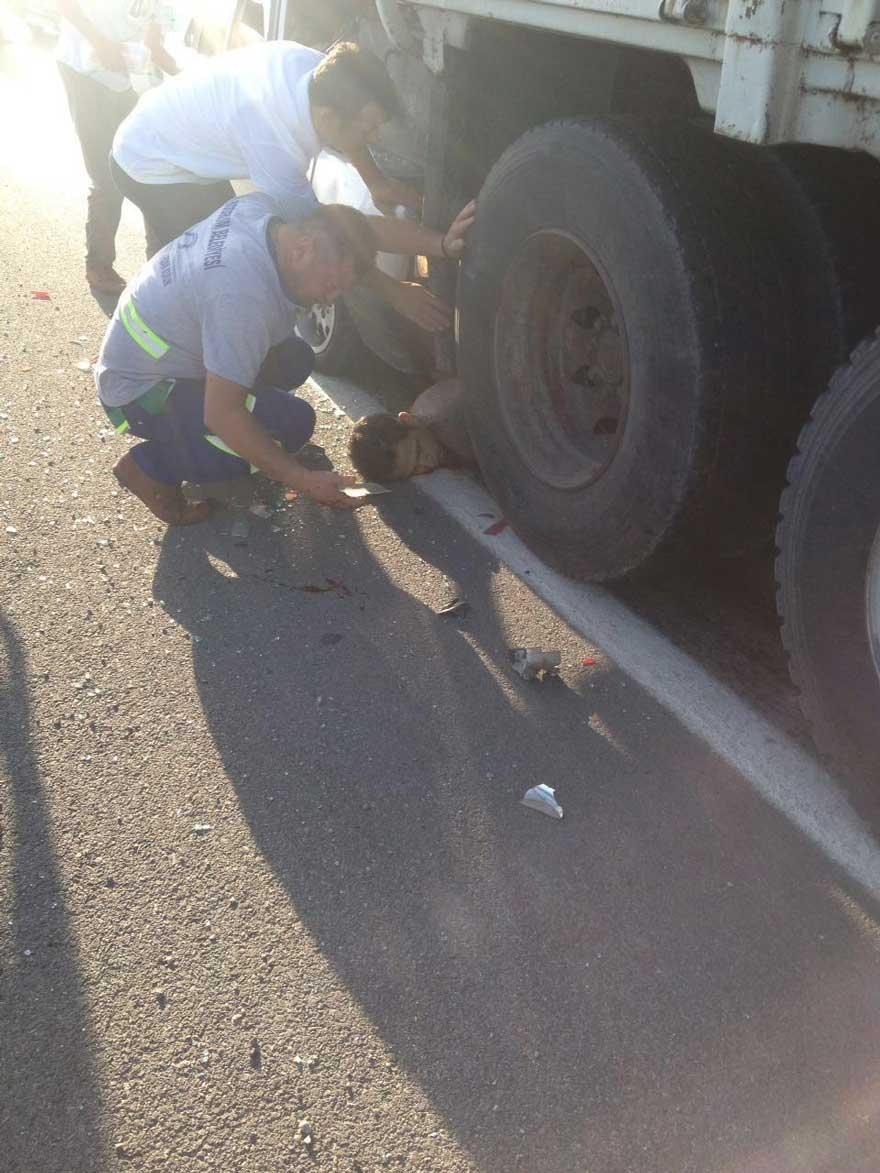 FOTO: İHA / Kazada motosiklet sürücüsü genç mucizevi bir şekilde otomobille kamyonun tekerleği arasındaki boşlukta kaldı.