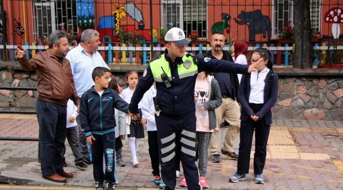 İlkokul öğrencilerini polis yolun karşısına geçirdi