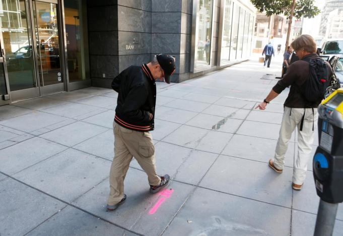 Pedestrians inspect cracks near the sinking Millennium Tower in San Francisco, California, U.S. September 14, 2016. REUTERS/Beck Diefenbach