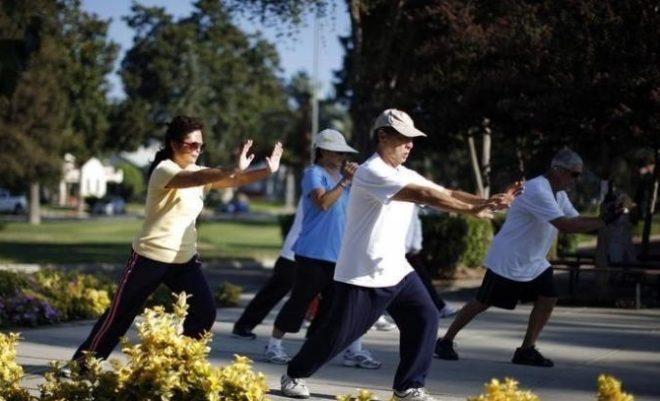 Parkta uzak doğu sporu tai chi yapan insanlar