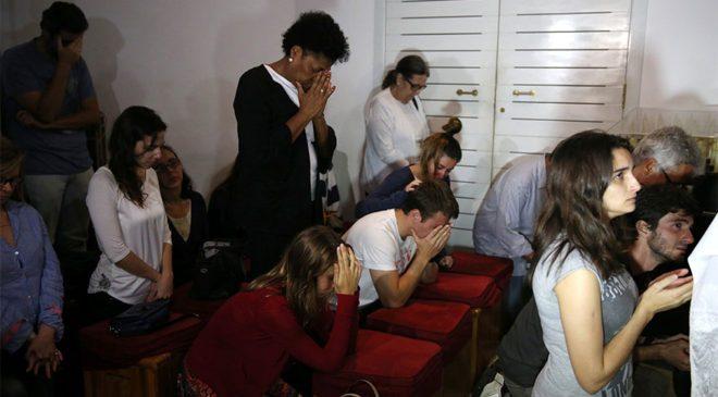 FOTO: REUTERS/ Gazeteci Guilherme Marques'in akrabaları, Rio de Janeiro'da dua ediyor.