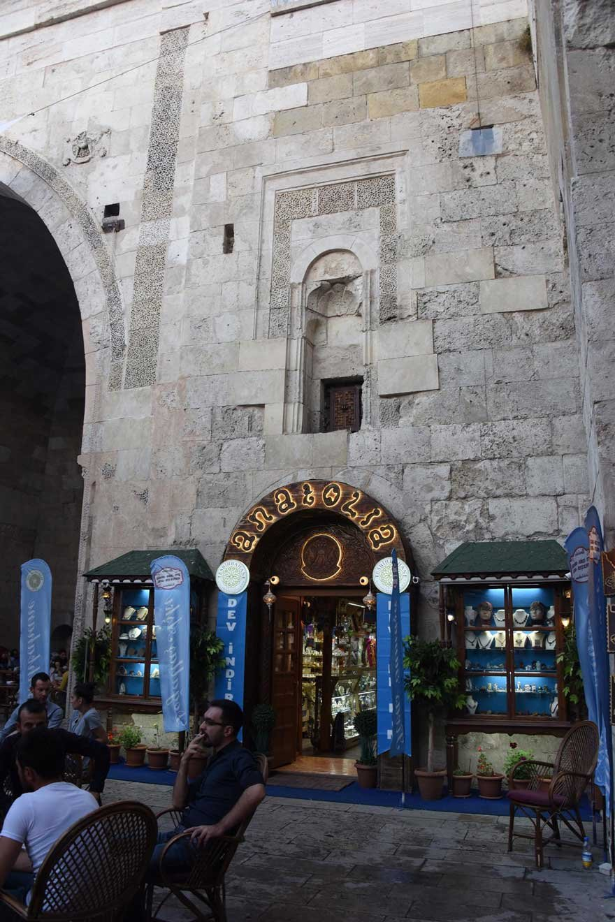 Hediyelik eşya satan dükkanın kapı ve pencereleri Çifte Minareli Medrese'nin duvarında...