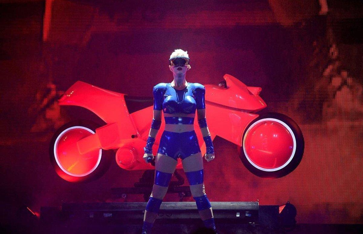 Bir süper kahraman gibi görünen Katy Perry Adam Selman'a ait çizgili mavi bir spor kıyafet giydi. Geleceğe Yolculuk filminden fırlamış gibi görünen Perry aksesuar olarak da ilginç bir gözlük tercih etmiş.