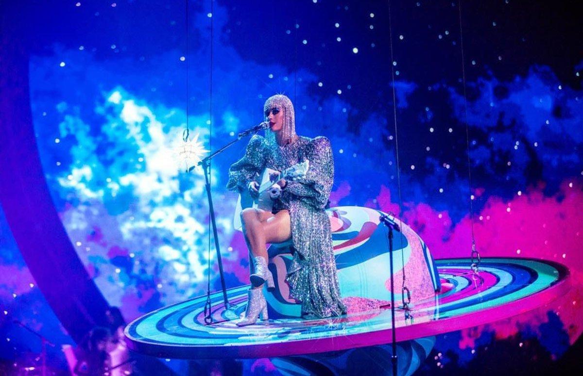 1980'leri andıran, Adam Selman imzalı vatkalı ışıltılı gümüş elbisesini, Katy Perry Collection markasından ışıltılı gümüş bir bot ile kombinleyen Katy Perry, taktığı gümüş peruk ile oldukça farklı görünüyor.
