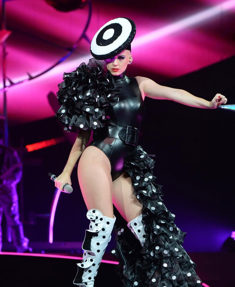 Konserde genel olarak Adam Selman tasarımları tercih eden Katy Perry, konserin sonlarına doğru yine aynı tasarımcıya ait bir kıyafet tercih etti. Deri mayo kostümünü Sergio Rossi diz üstü çizmelerle kombinleyen Perry harika bir görünüm elde etmiş.