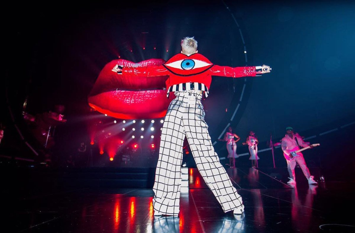Katy Perry, Johnny Wujek imzalı, sırtında büyük bir dudak ve göz görünümlü kırmızı ceketini yüksek bel bir palazzo pantolon ile kombinlemiş.