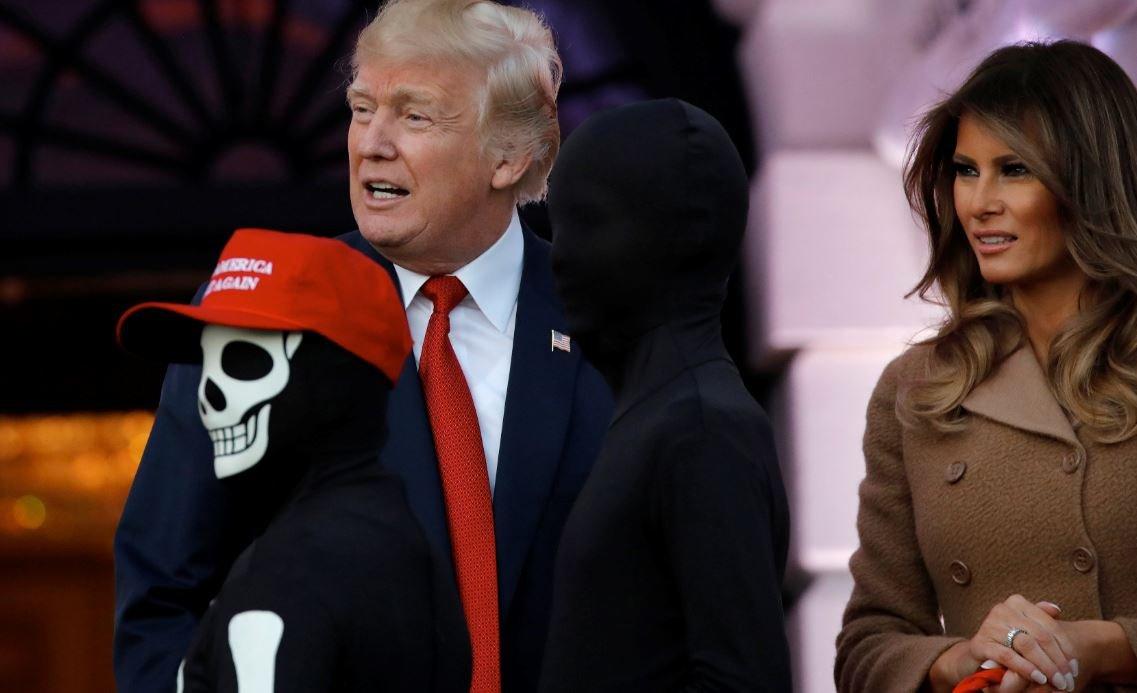 """Şapkasında """"Amerika'yı yine harika yap"""" sloganı olan küçük bir ziyaretçi iskelet kostümüyle Trump'tan şeker topladı."""