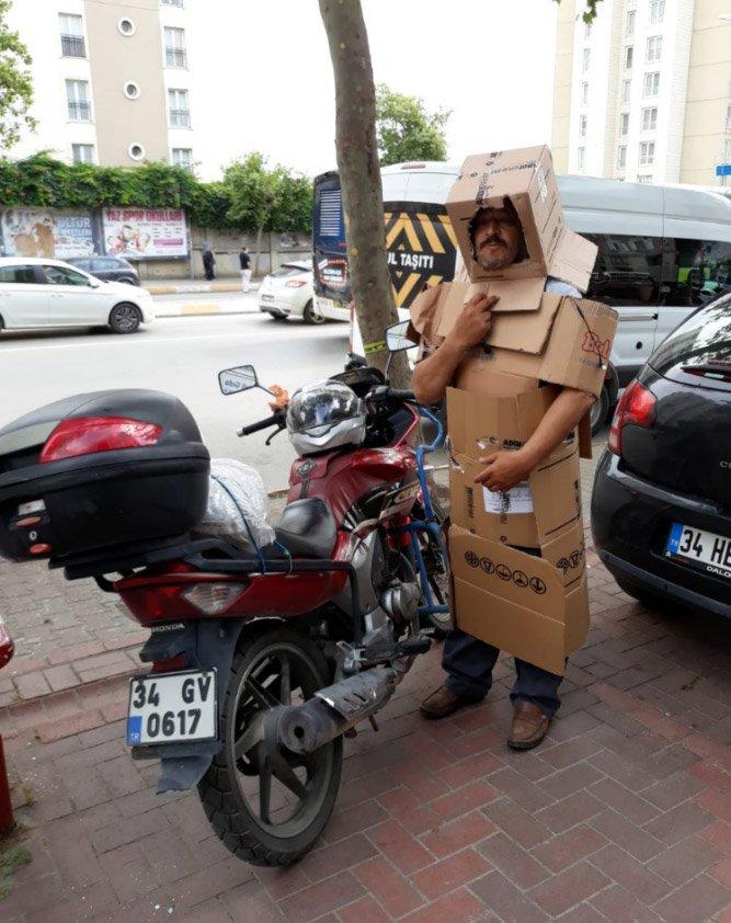 FOTO:AA - Dolur alarmına ilişkin en ilginç fotoğraf ise 'kendisini kartonla korumaya çalışan motosiklet sürücüsü' oldu.