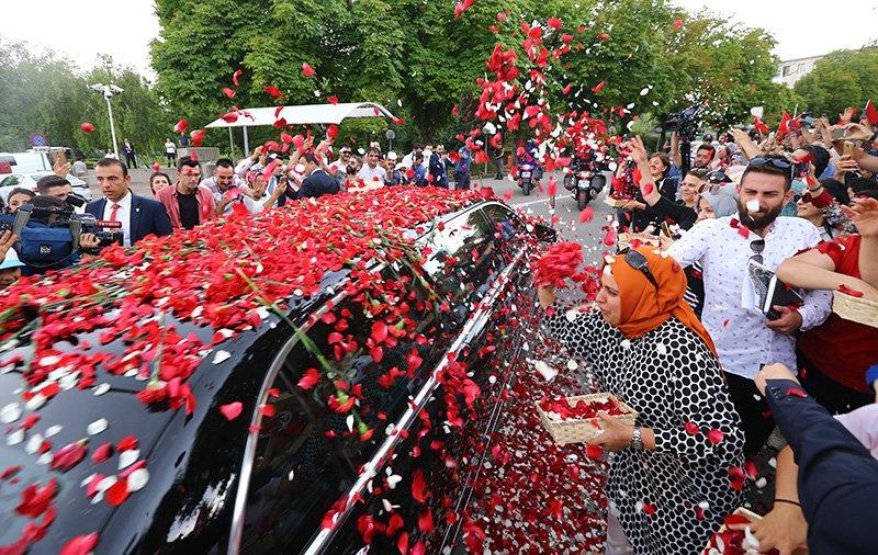 Erdoğan'ın makam aracının ön camı üzerine atılan çiçekler yüzünden neredeyse kapandı.