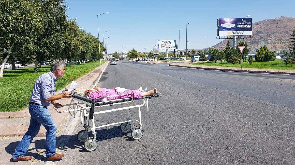 Ambulans verilmediğini iddia ettiği hastasını, sedye ile caddeye çıkardı