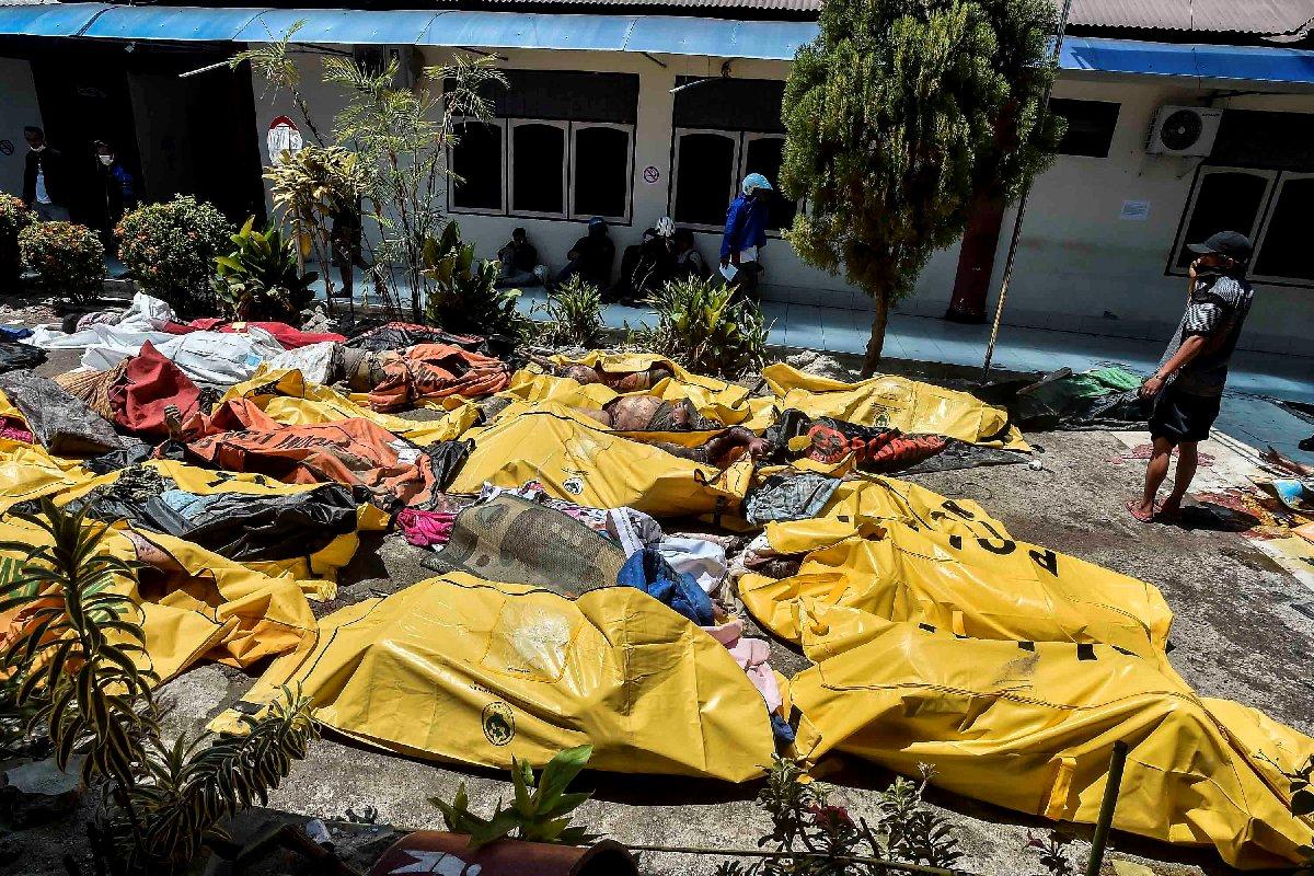 Peş peşe felaket yaşayan Endonezya'daki hastanelerde ve morglarda yer kalmadığı için cansız bedenler bahçeye çıkarıldı.