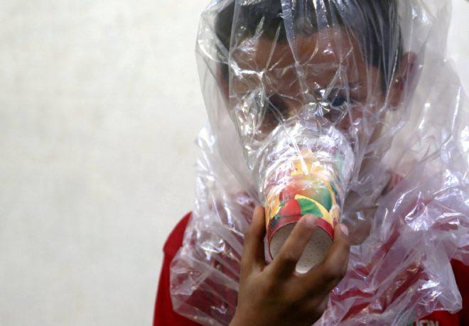 Çocuklar gaz maskelerini deniyor.