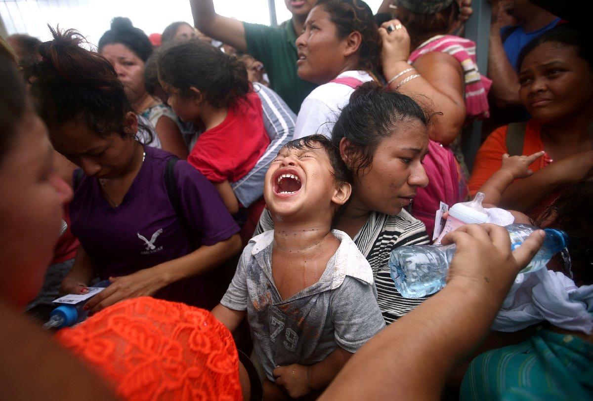 Ülkelerinden kaçan Guatemalalılardan bazıları, biber gazı sıkan Meksika polisinin ardından bayıldı.