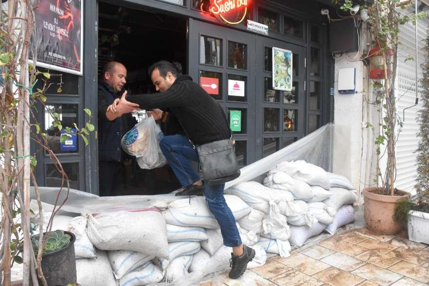 Vatandaşlar dükkanların önünde kum torbalarıyla önlem aldı. Foto: AA