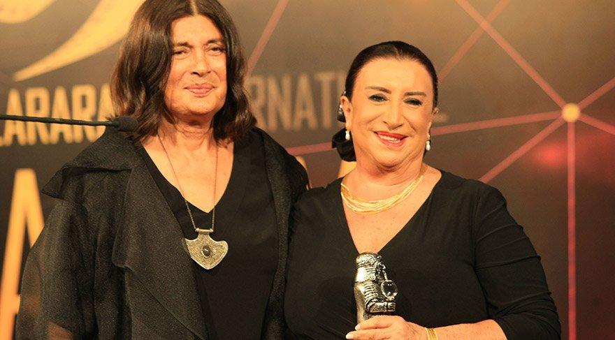 Sanatçı Şerif Sezer (solda), festivalde 'Onur Ödülü'ne layık görülen sanatçı Perran Kutman'a (sağda) ödülünü verdi. FOTO:AA