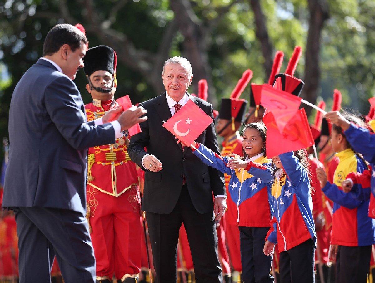 Maduro, daha sonra bayrağı çocuklara gösteriyor.