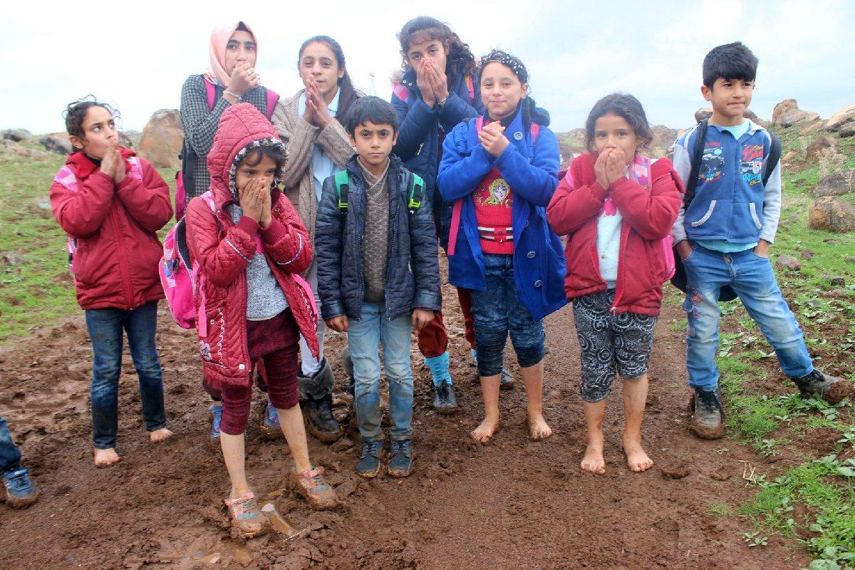 Öğrencilerden bazıları ıslanana ayakkabılarını çıkarıp öyle yürüyor. İHA