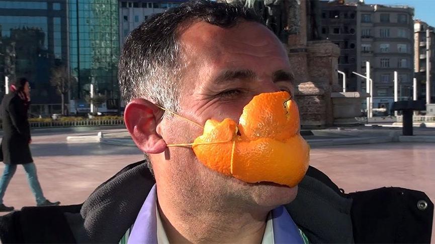 Portakaldan yaptığı maske ile türkü söyleye söyleye Taksim'de yürüdü