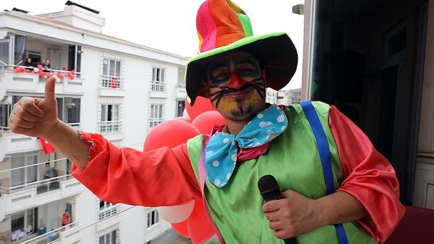 Palyaço kostümüyle balkondan çocukları eğlendirdi